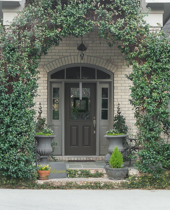 Ideas for decorating a spring front porch, featuring moss and other greenery and a Cricut-made'moss painted' Welcome sign.
